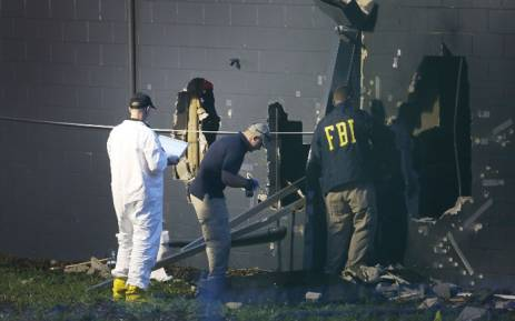 FBI agents investigate near the damaged rear wall of the Pulse Nightclub where Omar Mateen allegedly killed at least 50 people on 12 June, 2016 in Orlando, Florida. Picture: AFP.