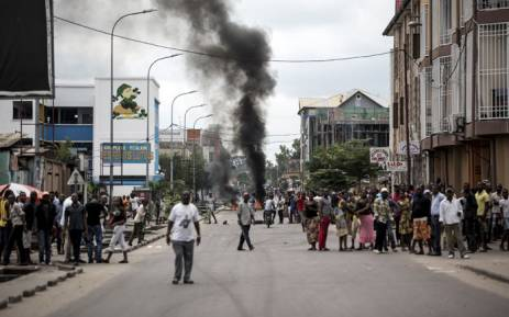 People look on as protesters burn tyres during a demonstration calling for the President of the Democratic Republic of the Congo (DRC)to step down on 21 January, 2018 in Kinshasa. Picture: AFP