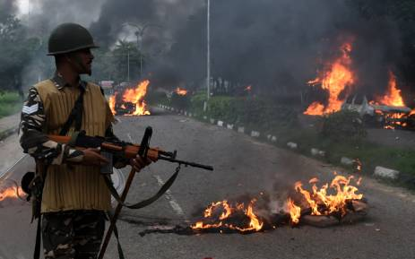 FILE: Indian security personnel looks at burning vehicles set alight by rioting followers of a religious leader convicted of rape in Panchkula on 25 August, 2017. Picture: AFP.