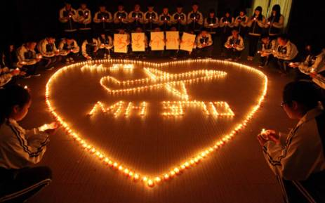 FILE: Hailiang International School lighting candles to pray for the passengers on the missing Malaysia Airlines flight MH370 in Zhuji, in China's Zhejiang province on 10 March 2014. Picture: AFP.