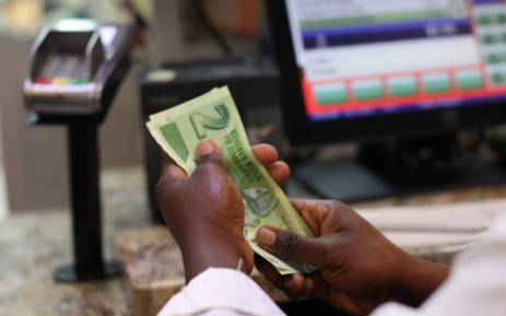 FILE: A man holds bond notes released by the Reserve Bank of Zimbabwe in Harare central business centre in 2016. Picture: AFP