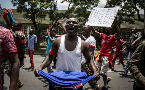 FILE: A protester holds a book of the DRC's constitution in defiance against President Joseph Kabila at a protest at the country's embassy in Pretoria in 2016. Picture: AFP.