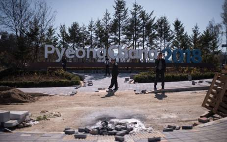 People stand before a sign for the Pyeongchang 2018 Winter Olympic games in the town of Hoenggye, South Korea on 31 October 2017. Picture: AFP