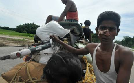 Injured Indian Muslim villagers move to relief camps from Gosaigaon village, at Kokrajhar district in the northeastern state of Assam on July 26, 2012. Picture: AFP.