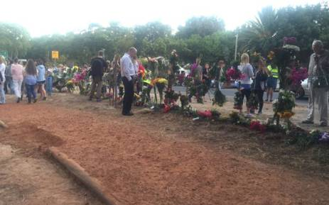 FILE: As hundreds of people silently make their way down a footpath in Tokai Forest, some wipe away tears and others cling to flowers. Picture: Monique Mortlock/EWN.