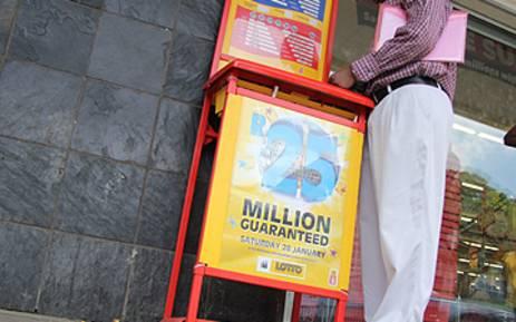 FILE: A man fills in a lotto form outside a lotto stand in Pretoria. Picture: EWN