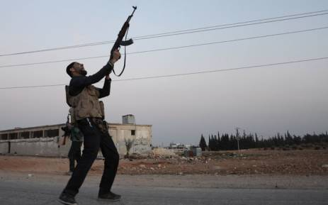 A Turkish-backed Syrian rebel fires off his gun in the north-western border town of al-Bab on 23 February 2017 after they fully captured the town from the Islamic State. Picture: AFP.