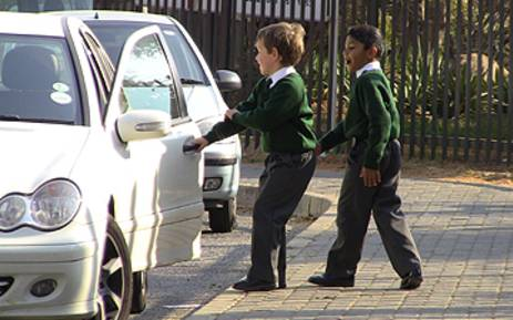 Two primary school boys are picked up outside Rivonia Primary. Picture: Tshepo Lesole/Eyewitness News.