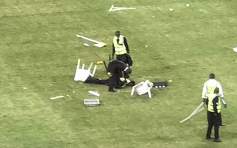 A security guard lies motionless on the ground after being attacked by angry Kaizer Chiefs fans after they invaded the pitch during the Nedbank Cup match against Free State Stars at Moses Mabhida on 21 April 2018. Picture: Screengrab