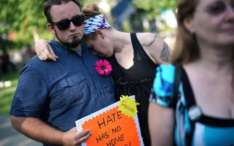 Krystin Rines (C) rests her head on her husband Tyler Rines' (L) shoulder during a vigil for those who were injured and died when a car plowed into a crowd of anti-fascist counter-demonstrators marching near a downtown shopping area 12 August 2017 in Charlottesville. Picture: AFP.