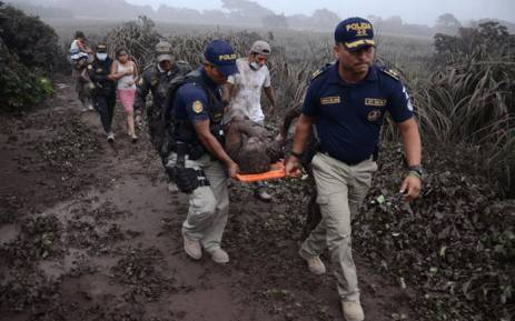 Police officers carry a wounded man after the eruption of the Fuego Volcano, in El Rodeo village, Escuintla department, 35 km south of Guatemala City on 3 June, 2018. Picture: AFP.