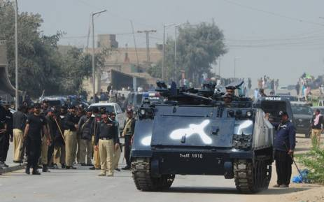 Pakistani policemen and an armoured vehicle try to reach mourners during a protest against a bomb attack on a shrine. Picture: AFP