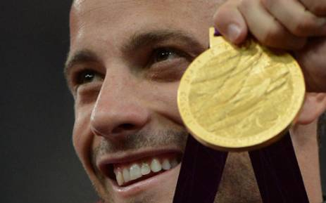 South Africa's Oscar Pistorius poses on the podium with his gold medal after winning the men's 400m - T44 final during the athletics competition at the London 2012 Paralympic Games on September 8, 2012. Picture: AFP.