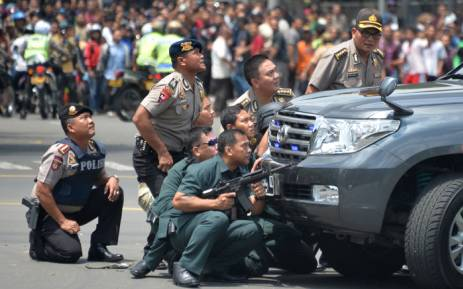 Indonesian police take position behind a vehicle as they pursue suspects after a series of blasts hit the Indonesia capital Jakarta on 14 January, 2016. Picture: AFP.