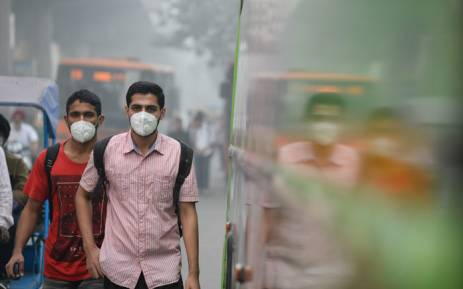 Indian commuters wear masks as they walk along a road amid heavy smog in New Delhi on November 9, 2017. Picture: AFP