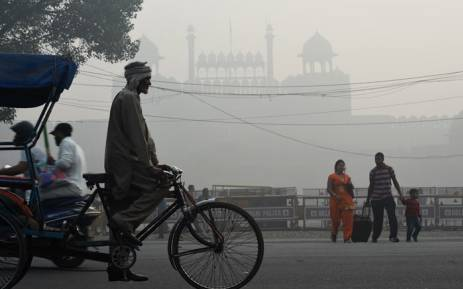 An Indian family crosses a road amid heavy smog in front of the Red Fort in New Delhi on 10 November 2017. Large swathes of India's northern states remained under dense smog that has shut hundreds of thousands of schools, disrupted air and railway services and forced residents to stay indoors. Picture: AFP.