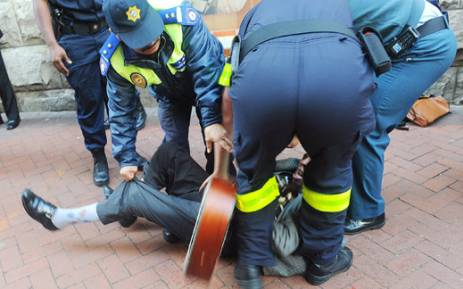 Police drag a blind busker across Greenmarket Square in Cape Town. Picture: Michael Walker/Cape Times