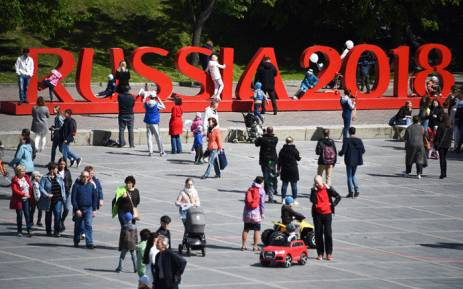 People walk in front of a sign reading Russia 2018 in Yekaterinburg on 12 June 2018, ahead of the Russia 2018 World Cup football tournament. Picture: AFP.