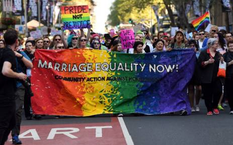Supporters hold a banner while marching as they attend a same-sex marriage rally in Sydney on September 10, 2017. Picture: AFP.
