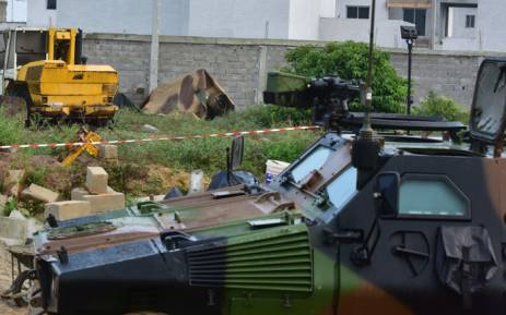 This photo taken on 11 July 2018 shows a French military vehicle in front of the debris covered by tarpaulin following the crash of a French army Gazelle helicopter close to a residential area, near Abidjan in the Ivory Coast, on 10 July 2018. Picture: AFP.