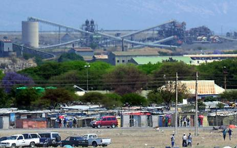 A picture taken on October 6, 2012 shows workers standing outside the Anglo American Platinum (Amplats) mine in Rustenburg. Picture: AFP