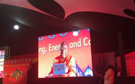President Cyril Ramaphosa is seen on the screen while addressing delegates at NUM congress in Boksburg. Picture: Qaanitah Hunter/EWN.