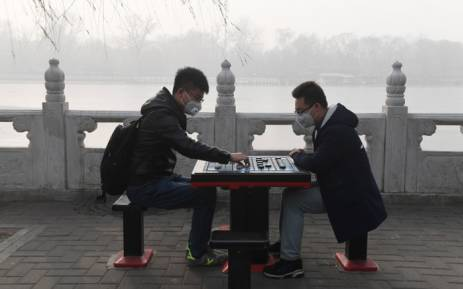 Two men play Chinese chess beside a lake on a heavily polluted day in Beijing on 1 January, 2017. Picture: AFP