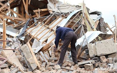 A Lenasia resident picks up bricks from his demolished house. Picture: Taurai Maduna/EWN