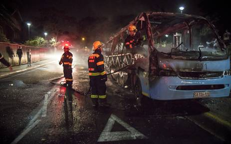 Firefighters extinguish a Jammie Shuttle that was torched by protesting #RhodesMustFall students at UCT. Picture: Thomas Holder/EWN