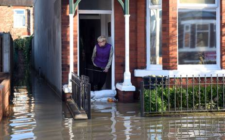 A woman looks out from a flooded property adjacent to the River Foss which burst its banks in York, northern England, on 27 December, 2015. Picture: AFP.