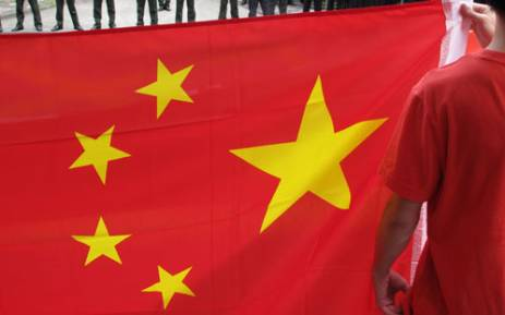 A man holds a Chinese flag as protesters take part in an anti-Japanese protest outside the Japanese consulate, guarded by police (in background), in Shanghai on August 16, 2012. Anti-Japanese protests were staged in Shanghai and Beijing following the arrest of a group of pro-China activists who landed on a disputed archipelago known as Diaoyu in China and Senkaku in Japan. Picture: AFP.