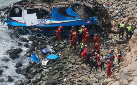 Handout picture released by Peruvian agency Andina showing rescuers, police and firefighters working at the scene after a bus plunged around 100 meters over a cliff after colliding with a truck on a coastal highway near Pasamayo. Picture: HO/ANDINA/AFP.