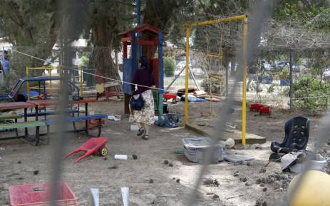 An Israeli journalist inspects the damage in a kindergarten yard, after mortar shells fired from the Gaza Strip exploded near it, in the southern Israeli Kibbutz of Ein Hashlosha on 29 May, 2018. Picture: AFP