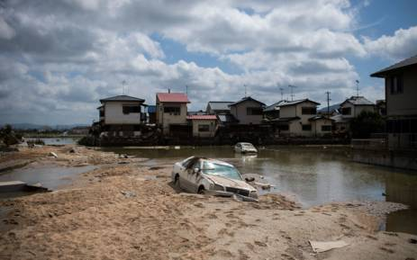 A damaged car is seen stuck in the mud in a flood hit area in Mabi, Okayama prefecture on 10 July, 2018. Picture: AFP