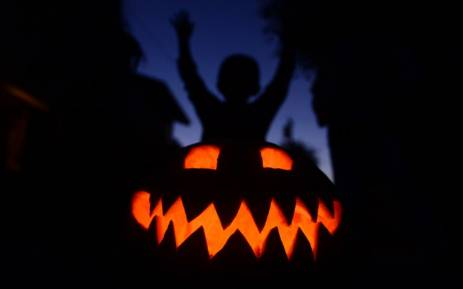 Children play behind a pumpkin carved and lit for Halloween on 30 October 2013 in Monterey Park, California. Picture: AFP/Frederic J. Brown