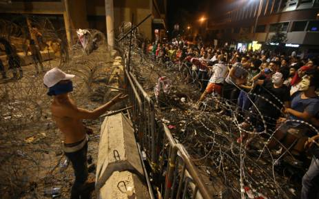 Lebanese protesters stand on both sides of the barbed wire separating them from the governmental palace as some of them managed to get through them at the end of a mass rally against a political class seen as corrupt and incapable of providing basic services on 29 August, 2015 at the iconic Martyrs Square in Beirut. Picture: AFP.