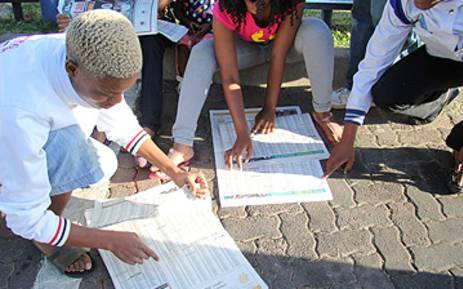 FILE: Students search for matric results in the newspaper. Picture: EWN