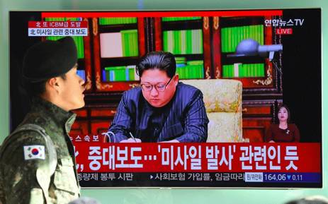 A South Korean soldier walks past a television news screen showing North Korean leader Kim Jong-Un approving the country's new ICBM test, at a railway station in Seoul on 29 November 2017. Picture: AFP.