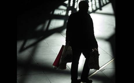 A shopper carries bags containing his purchases through the Trafford Centre shopping mall on 'Black Friday' at the Trafford Centre shopping mall in Manchester. Picture: AFP.