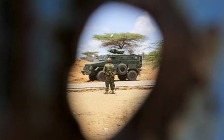 A Kenyan soldier serving with the AMISOM is pictured through a bullet hole in the gate of the compound housing the former offices of the UN's refugee agency in Kismayo, southern Somalia. Picture: UN Photo.
