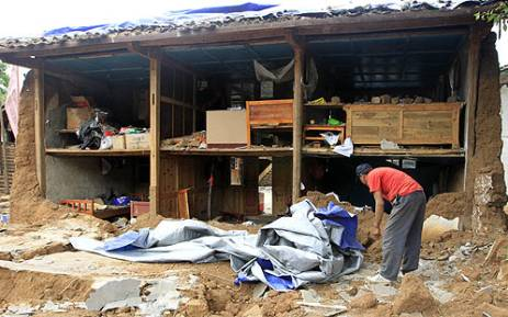 A villager salvages his belongings outside his earthquake damaged home in China. Picture: AFP.