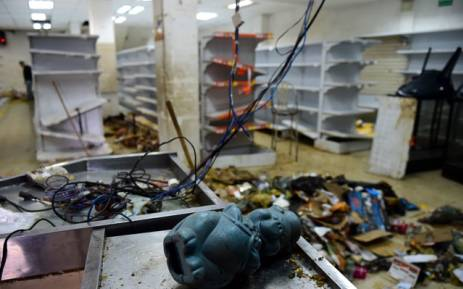 The view of damages caused by looters in a supermarket in Caracas on 21 April 2017 after demonstrations against the government of Venezuelan President Nicolas Maduro. Venezuela was rocked overnight by fresh violence in anti-government protests that have now claimed nine lives in three weeks, as an official reported Friday the fatal shooting of another man. Picture:  AFP.