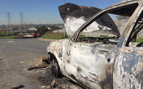 Hundreds of protesters set alight two vehicles at George Goch hostel in the Joburg CBD during an early morning demonstration. Picture: Vumani Mkhize/EWN.
