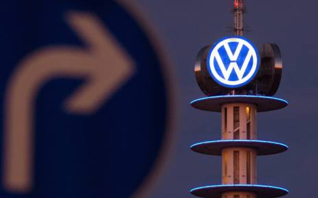 A street sign can be seen in front of the illuminated logo of German car maker Volkswagen (VW) on 10 December, 2015 in Hanover, central Germany. Picture: AFP.