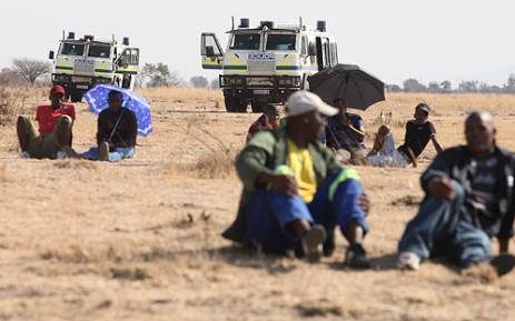 Striking Lonmin workers await news from the leaders, as police keep a close watch nearby. Picture: Taurai Maduna/EWN.