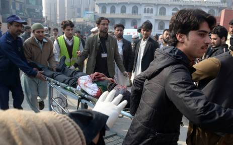 FILE: Pakistani men carry an injured student to a hospital following an attack by Taliban gunmen on a school in Peshawar on 16 December, 2014. Picture: AFP.