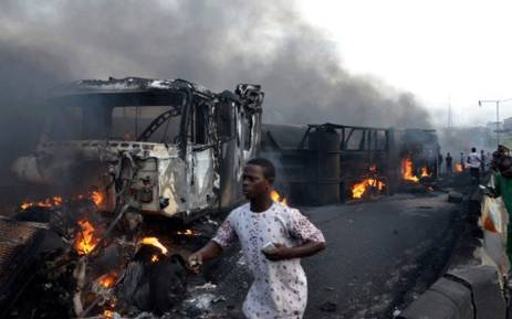 Passersby walk amid burned cars after an oil tanker exploded on a highway on June 28, 2018 in Lagos killing nine people in a huge blaze. Picture: AFP.