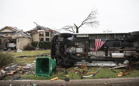 An American flag placed by first responders is seen 27 December, 2015 in the aftermath of a tornado in Rowlett, Texas. At least 11 people lost their lives as tornadoes tore through Texas, authorities said, as they searched home to home for possible more victims of the freak storms lashing the southern United States. Picture: AFP.