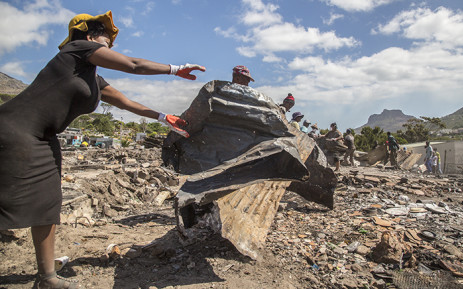 """FILE: """"Residents of the Imizamo Yethu informal settlement in Hout Bay, Cape Town, help to clear the rubble on 28 December 2015 after a fire ripped through a section. Picture: Aletta Harrison/EWN"""