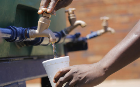 A young boy fills his cup from a water tanker in Coronation, Johannesburg, as South Africa faces water shortages due to drought. Picture: EPA/Kim Ludbrook